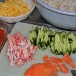 Потом готовим остальные продукты, какие лично вам хочется положить в сегодняшний вариант. Нам сегодня захотелось, помимо уже упомянутых огурца и омлета, подкопченого лосося, крабового мяса (не палки-камабоко, а настоящий краб) и икры. Что надо - режем также удобными кусками-полосочками