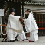 Мико подает священнику соломенную куклу
