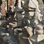 В основании колокола стоят старые и побитые статуи будд