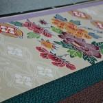 Это бингата 紅型, способ окрашивания тканей, разработанный на Окинаве. Отличается яркостью и чистотой цветов. И мотивами, заимствованными из соседнего Китая
