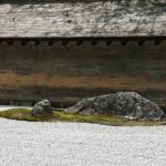 """Кажется, на оборотной стороне этого большого камня однажды были обнаружены выбитые имена - Котаро и Дзиро. Судя по отсутствию фамилий, имена могли принадлежать людям из """"неприкасаемых"""" каварамоно (садовников и каменотесов). Был ли Сад камней Рёан-дзи спроектирован ими или они только обрабатывали камни для него - неизвестно"""